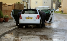 Couple getting flood water out of their family car
