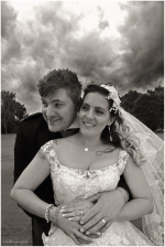 Black and white portrait of smiling bride and groom with a stormy sky behind them
