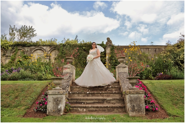 Bride standing on steps in the garden with a breeze in her veil