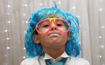 little boy wearing funny glasses and a wig at a wedding party