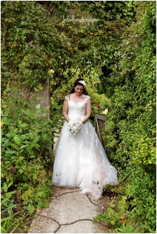 Bride standing surrounded by green plants and trees