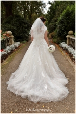 A photograph of the back of a bride's wedding dress in Dewstow Gardens