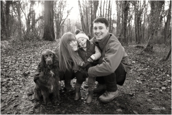 black and white photo of family with their dog