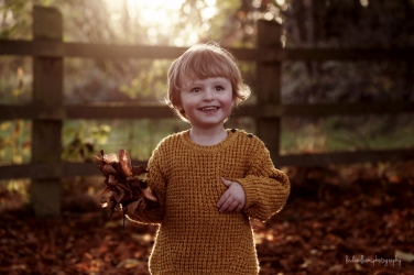 little boy in the autumn leaves