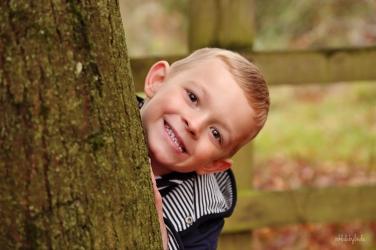 portrait of little boy playing hide and seek