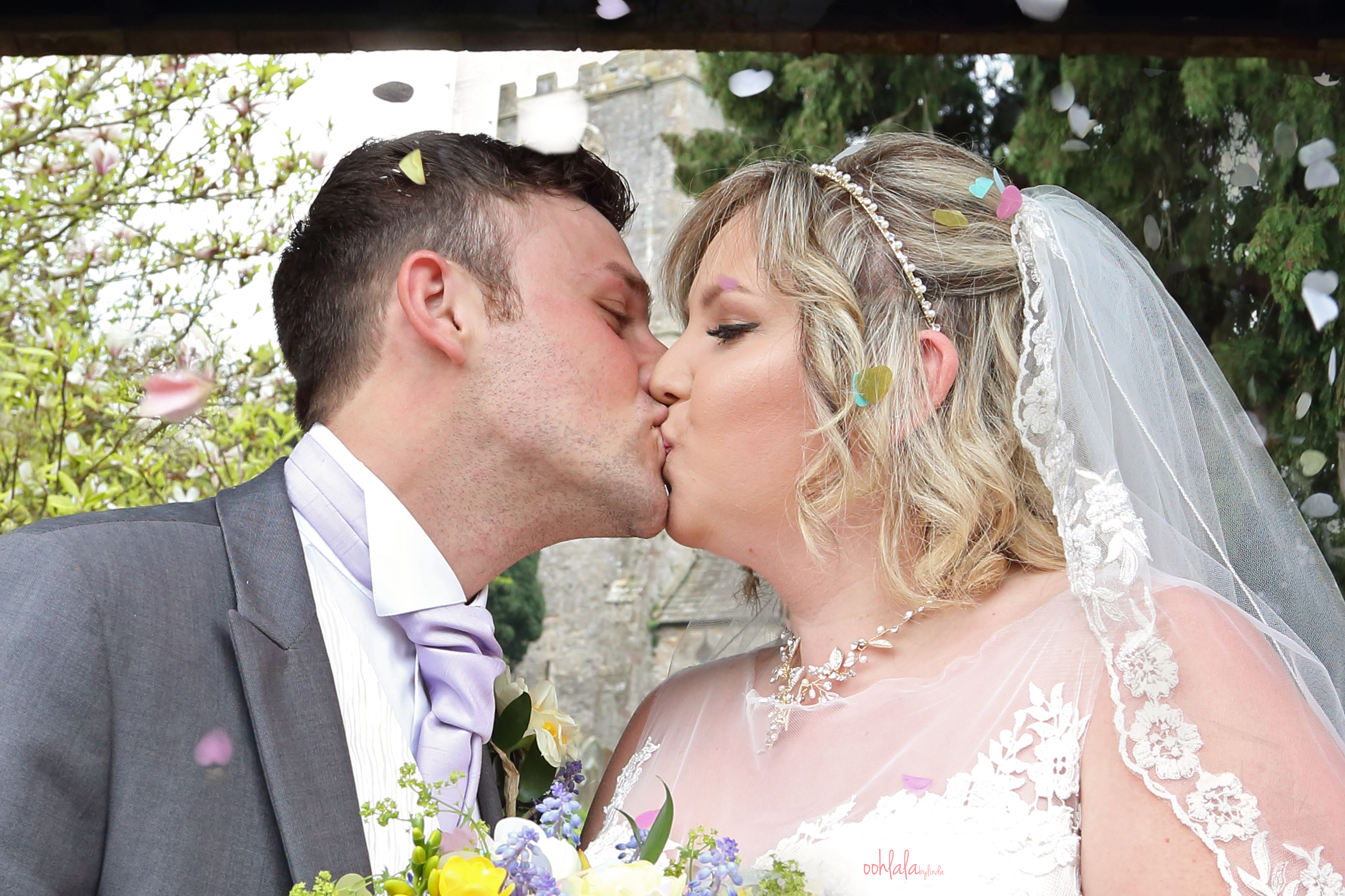 Bride and Groom kissing under confetti