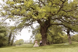 Bride and groom holding hands under a tree