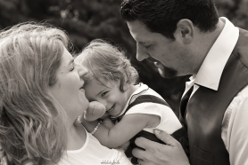black and white family portrait of parents with little girl laughing