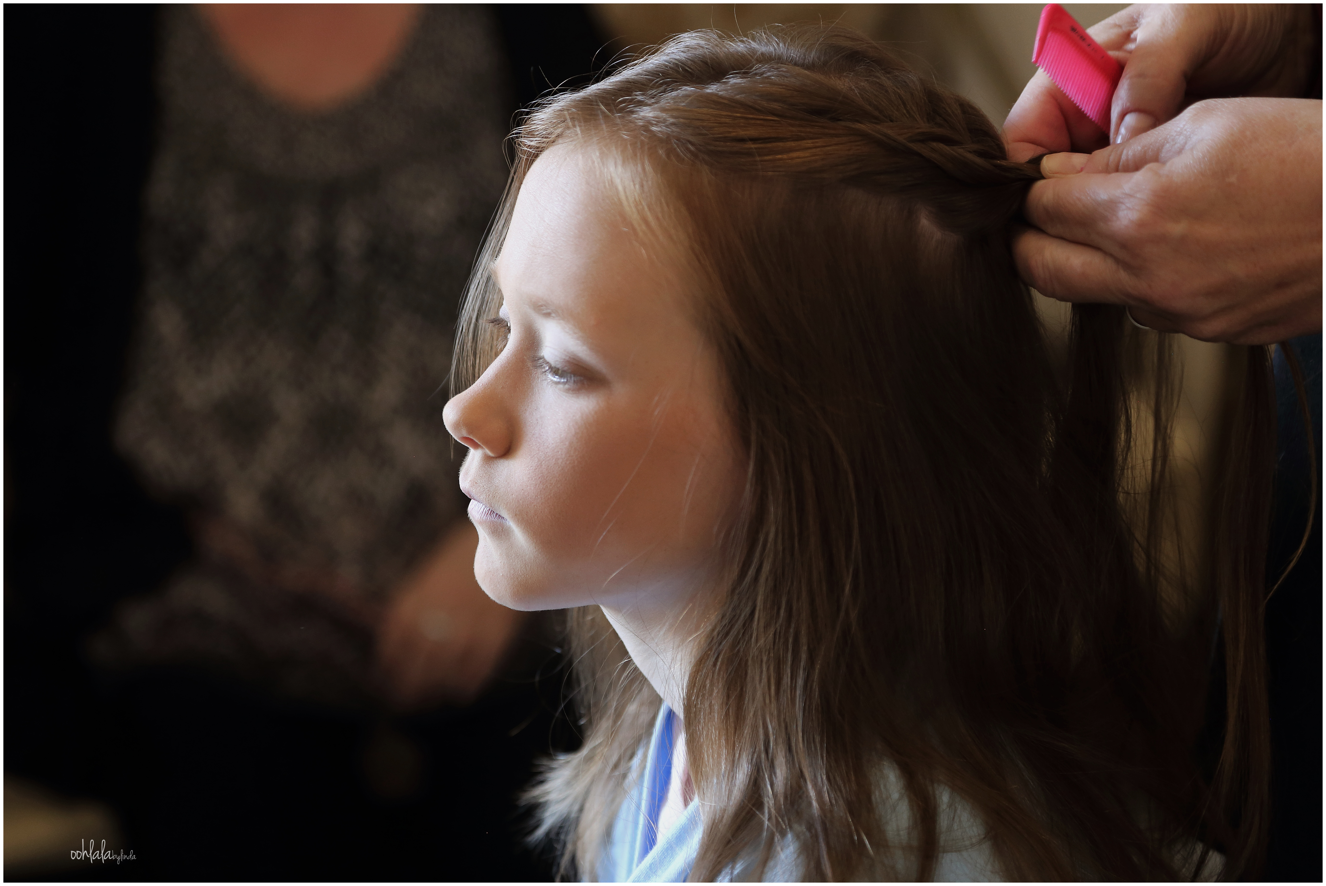 bridesmaid having her hair done during photography of bridal preparations
