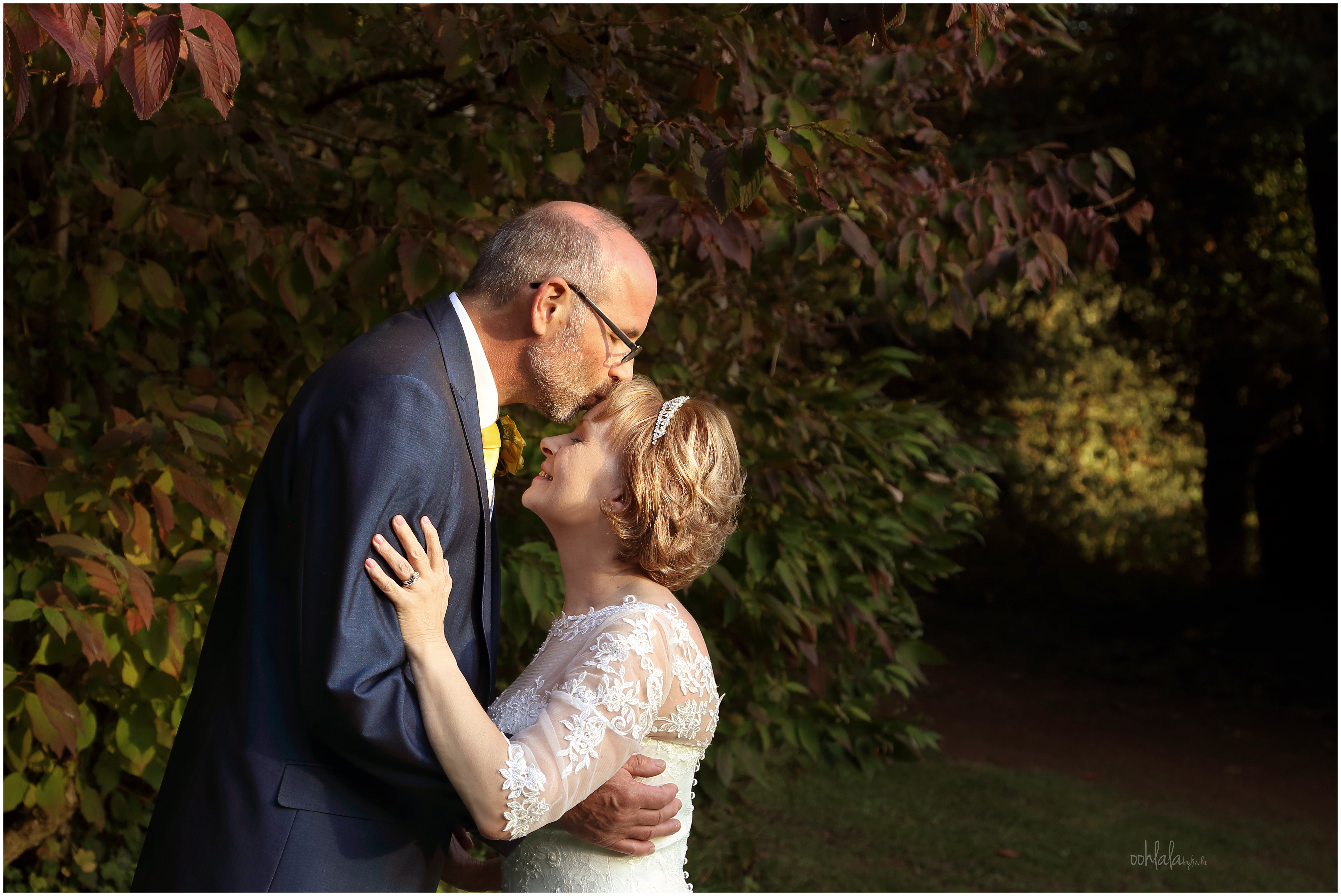 bridegroom kissing bride on top of her head in the gardens of wedding venue Caer Llan for a romantic photograph