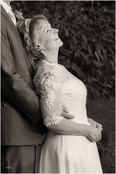 black and white photograph of bride laughing with her new husband at Caer Llan Monmouthshire