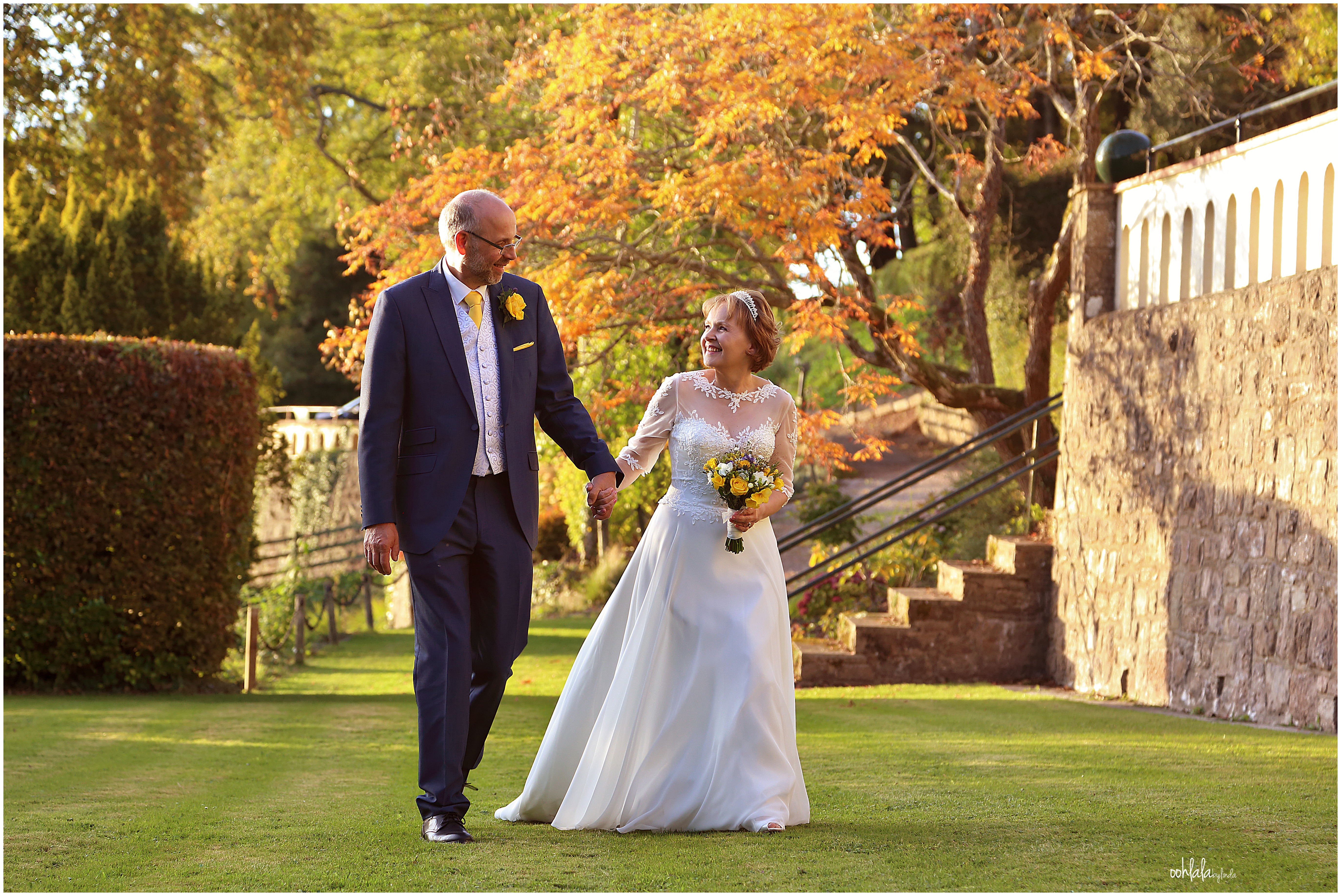 bride and groom in the gardens of the beautiful caer Llan at their wedding