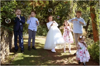 children at a wedding at Caer Llan blowing bubbles in the sunshine