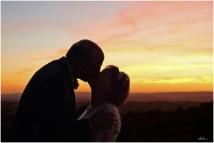 bride and groom romantically kissing in the sunset in monmouthshire