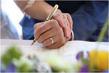 hands of bride and groom signing the register, showing wedding rings