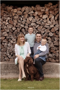 family group photographed sitting near woodpile
