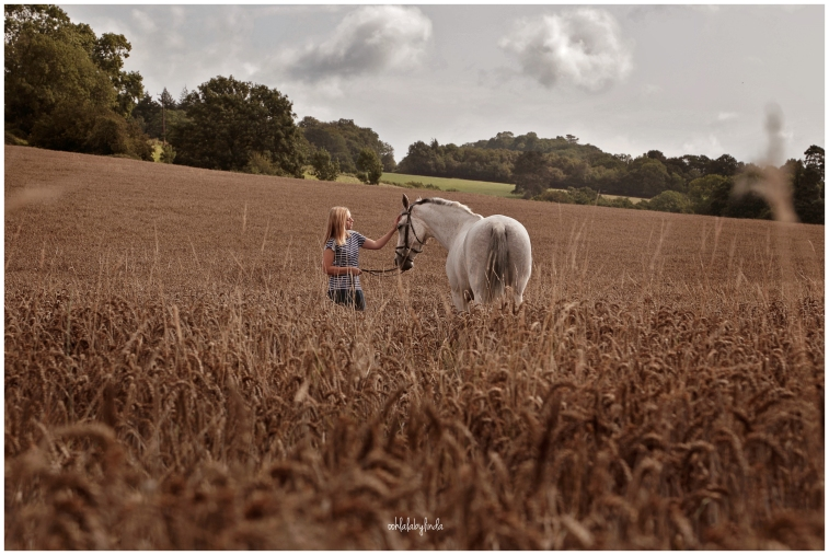 photograph of girl with her horse in a wheatfield