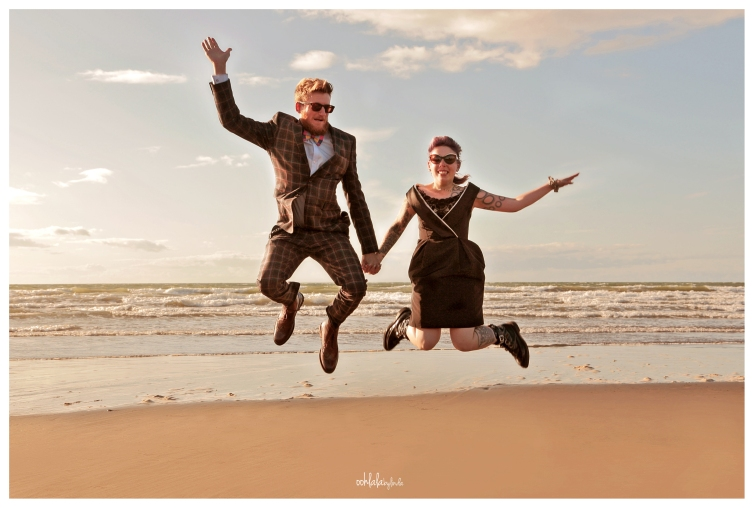 bride and groom jumping for joy on the beach