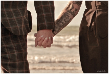 bride qand groom hold hands on the beach