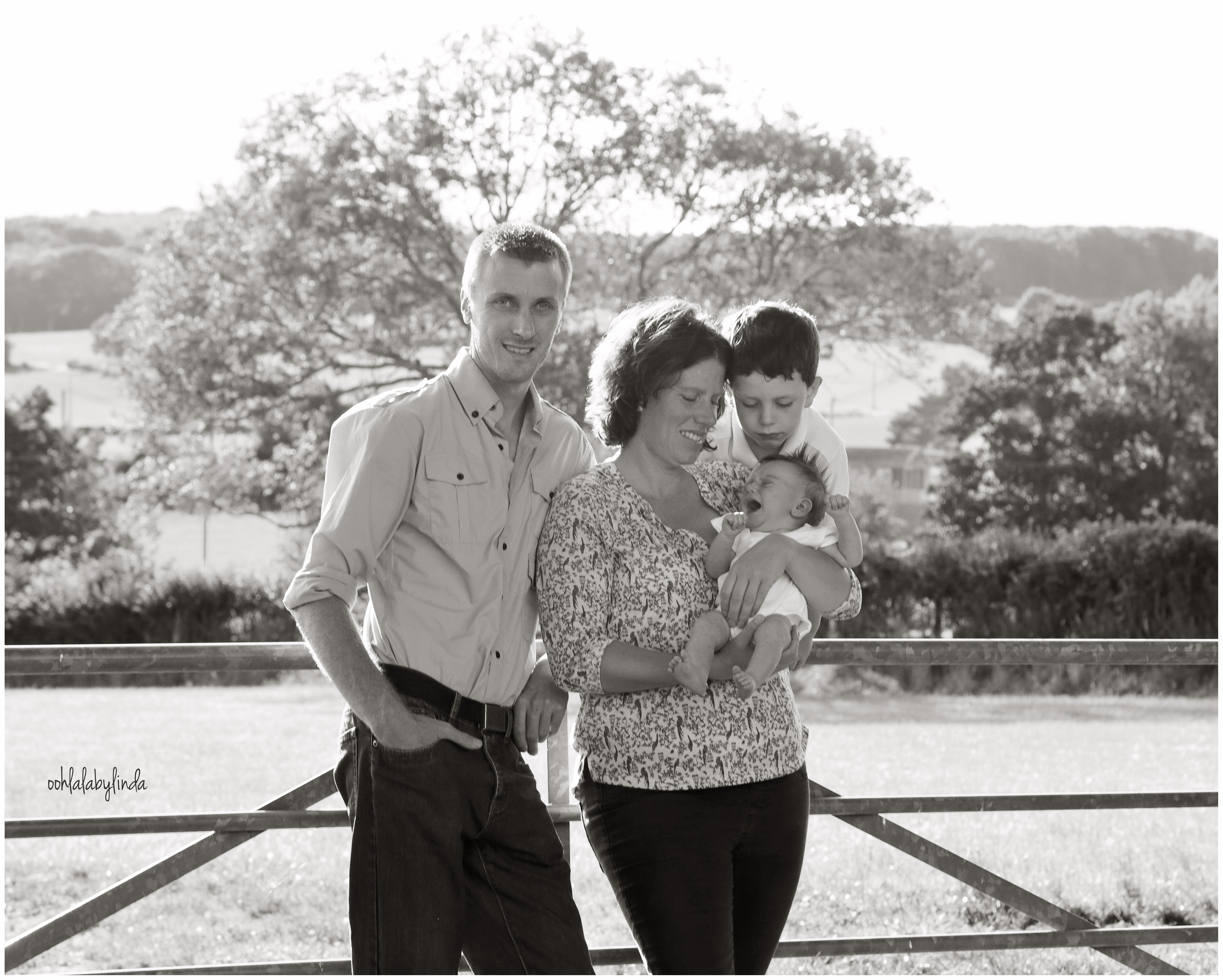 Black and white photograph of family with new baby outdoors
