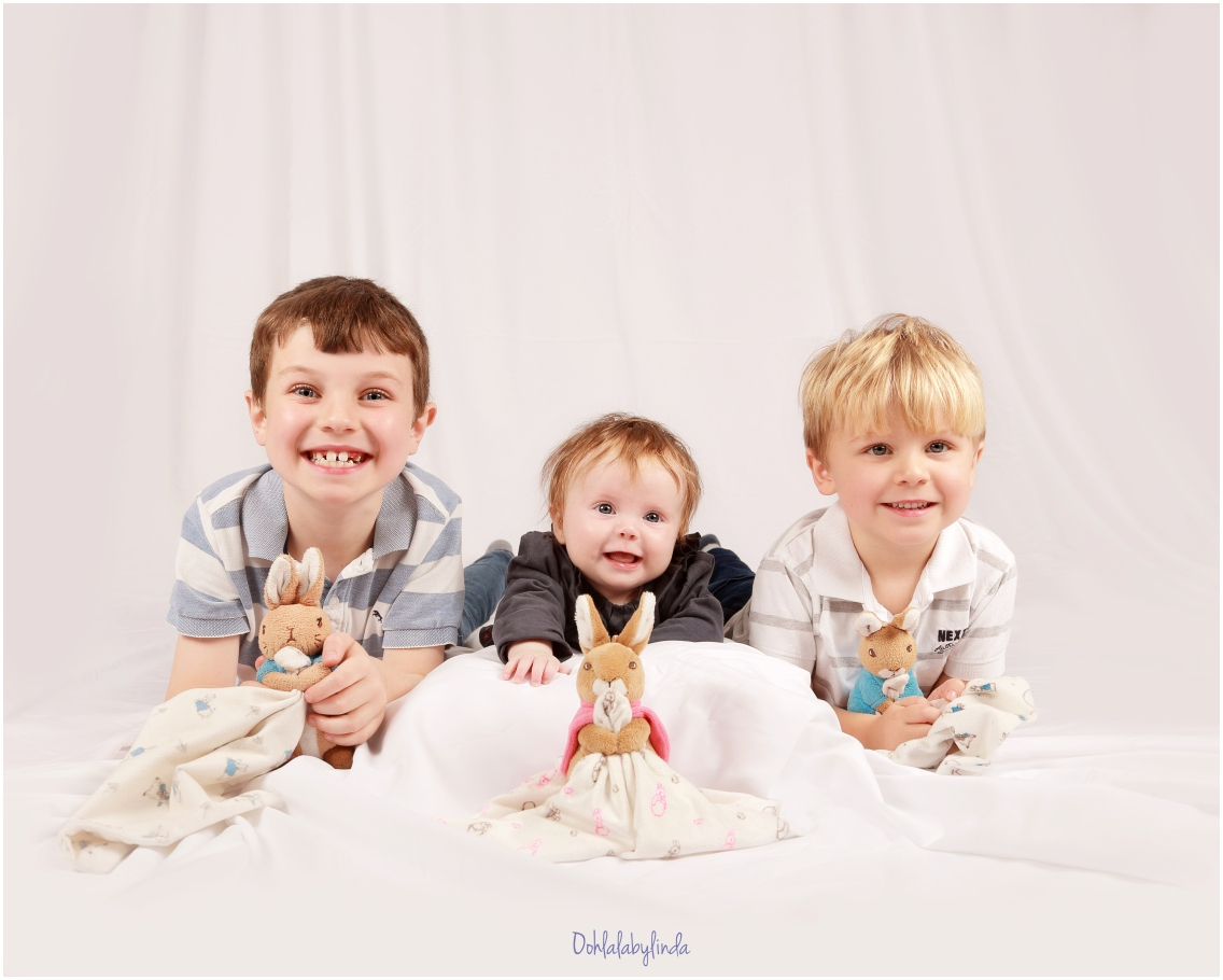 studio portrait of three children, two little boys and their baby sister