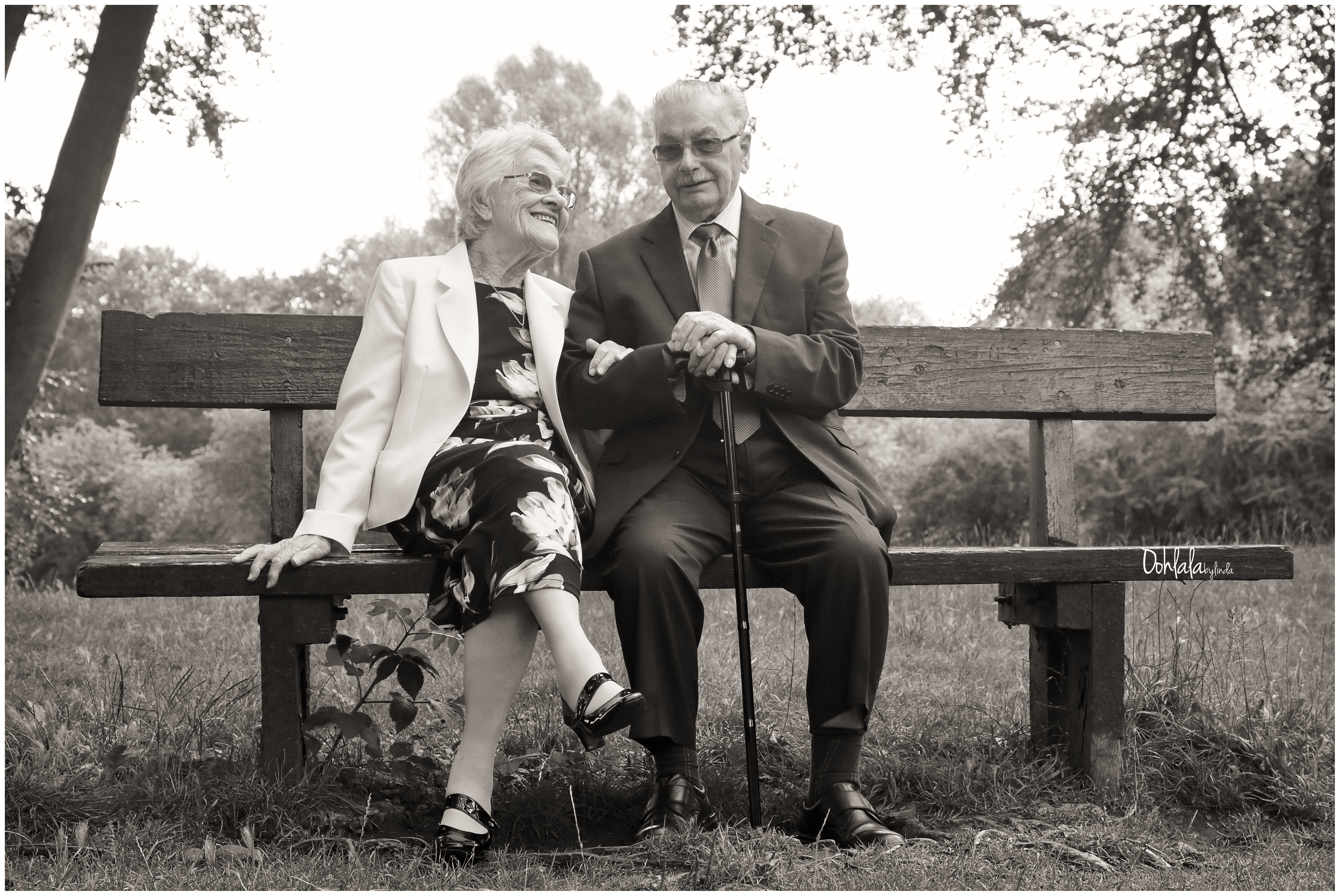 black and white portrait of elderly couple sat on bench
